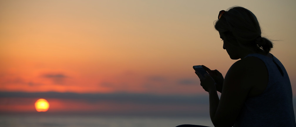 A women looks at her mobile phone as the sun sets over the ocean in  Encinitas, California, U.S., July 5, 2017.