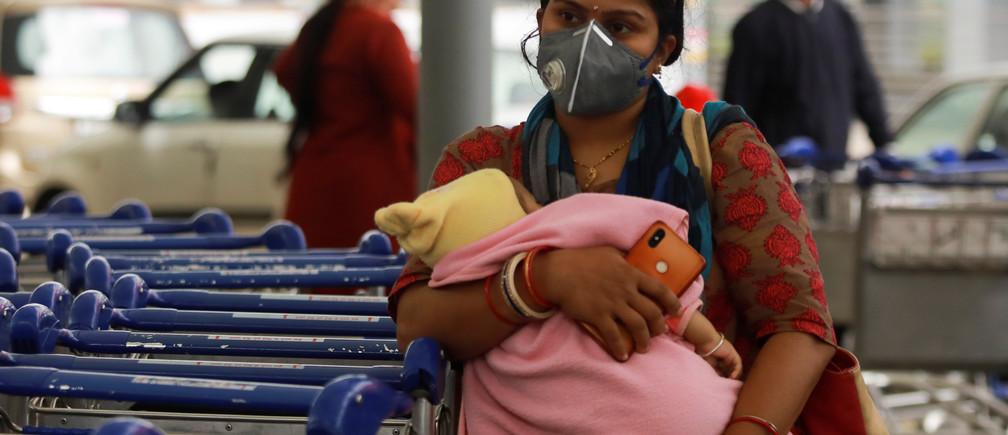 Una pasajera que lleva una máscara protectora sostiene a un bebé mientras espera fuera de un aeropuerto tras un brote de la enfermedad coronavirus (COVID-19), en Nueva Delhi, India, el 14 de marzo de 2020.