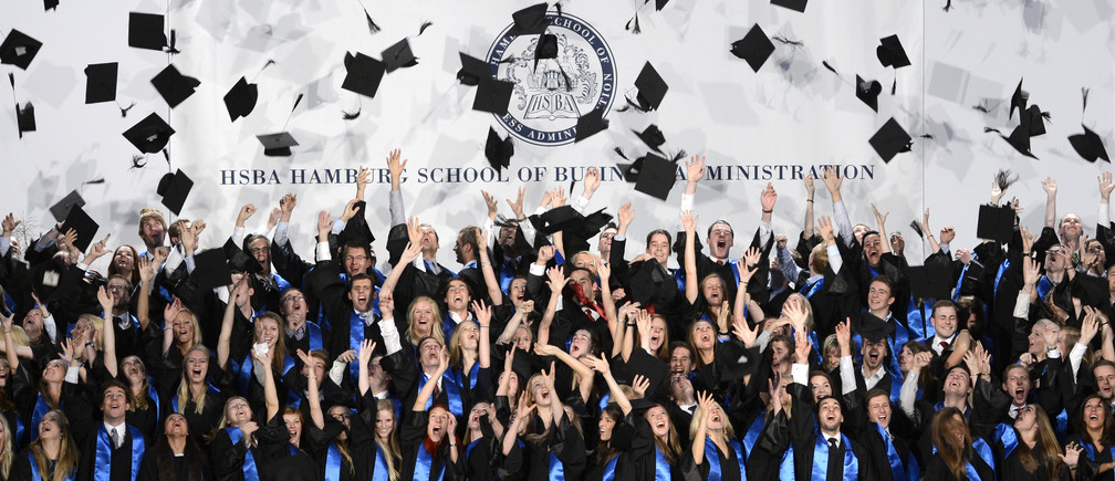 Students throw their hats after the graduation ceremony at the Hamburg School of Business Administration in Hamburg, September 26, 2012.