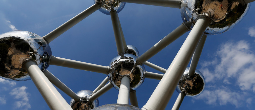 A plane flies over Brussels' Atomium building, a metal structure built in the form of a crystal of iron, at the opening of the exhibition on Belgian surrealist painter Rene Magritte, Belgium September 21, 2017. REUTERS/Francois Lenoir/www.atomium.be-SABAM Belgium 2017 EDITORIAL USE ONLY, NOT FOR SALE FOR MARKETING OR ADVERTISING CAMPAIGNS. NO RESALES. - RC1E5BD11460