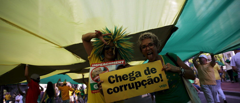 "Demonstrators hold a banner reading ""Enough of Corruption"" during a protest against Brazil's President Dilma Rousseff at Paulista Avenue in Sao Paulo"