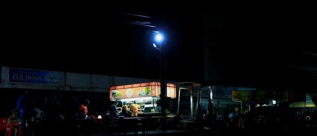 Street food vendors whose stalls' power is supplied by generators, work during a blackout in Maracaibo, Venezuela March 31, 2019. Picture taken March 31, 2019. REUTERS/Isaac Urrutia - RC1A97BCBC30