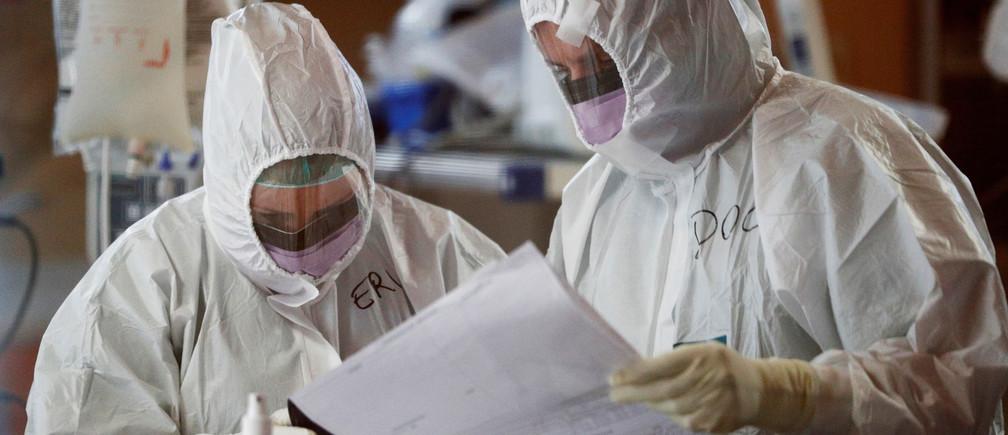 Trabajadores de la salud con trajes protectores revisan un documento mientras tratan a pacientes que sufren de la enfermedad coronavirus (COVID-19) en una unidad de cuidados intensivos del hospital Casalpalocco, un hospital de Roma que se ha dedicado a tratar casos de la enfermedad, Italia, 24 de marzo de 2020.