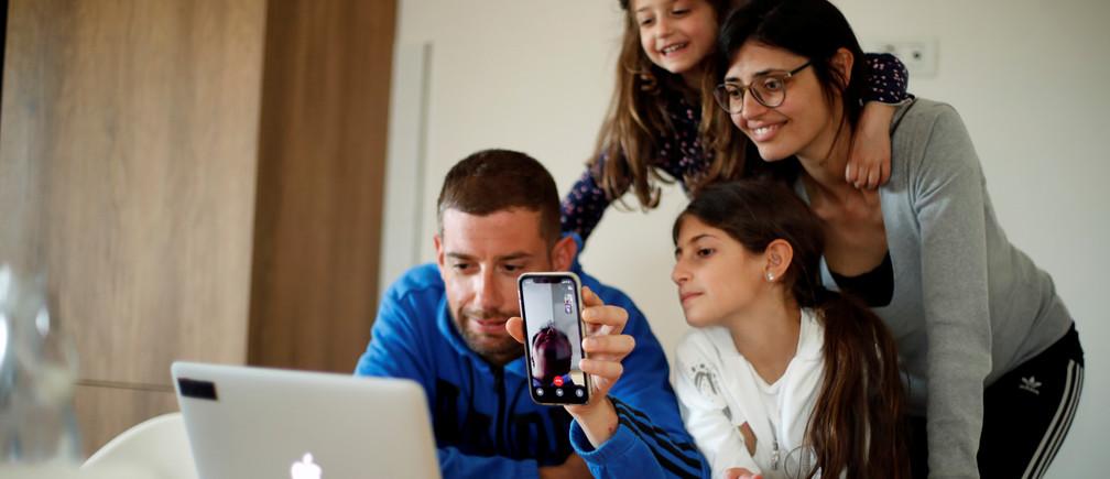 Miembros de la familia hablan con sus parientes en una videollamada usando sus dispositivos electrónicos, durante el brote de la enfermedad coronavirus (COVID-19) en Cisternino, al sur de Italia, el 13 de abril de 2020.