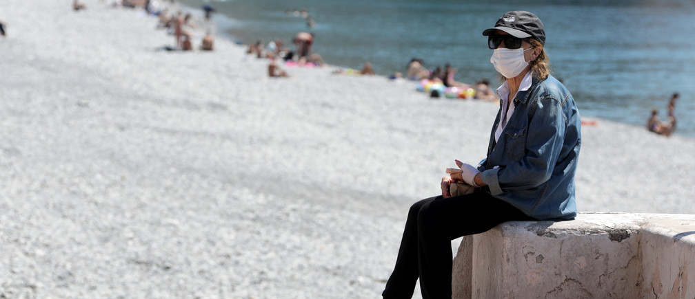 A  woman, wearing a protective face mask, sits on the beach of the Promenade des Anglais, after France reopened its beaches to the public as it softens its strict lockdown rules following the outbreak of the coronavirus disease (COVID-19), in Nice, France, May  21, 2020.   REUTERS/Eric Gaillard - RC2ZSG9X2R5J