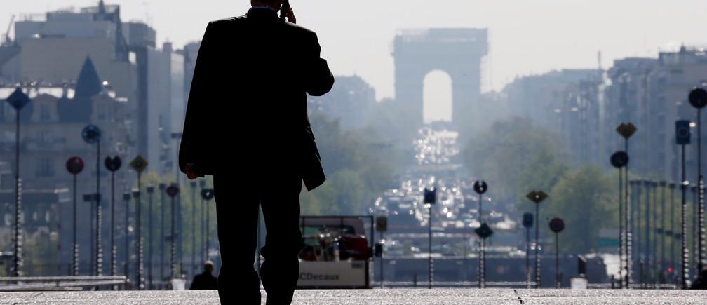 A businessman walks on the esplanade of La Defense.