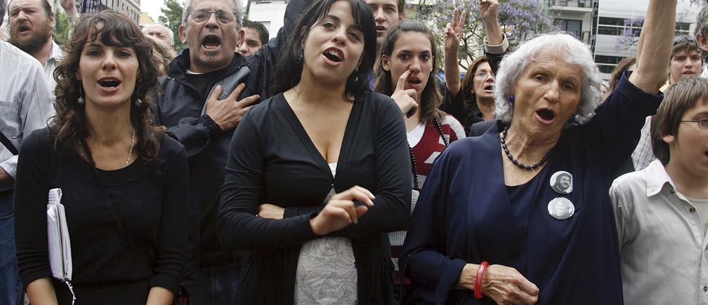 Argentina's newly-elected congresswoman Victoria Donda Perez (C) takes part in a political rally in front of the Naval Mechanics School building, Argentina's infamous torture center also known as ESMA, in Buenos Aires November 17, 2007. Donda, born to political prisoners during Argentina's dirty war then illegally adopted and robbed of her identity, swears to deepen the country's commitment to human rights when she takes her new seat in Congress next week. Of more than 80 people who have recovered their identities after being born in captivity during the 1976-1983 military dictatorship and then adopted by military families or their friends, Donda is the first to become a lawmaker. Picture taken November 17.  REUTERS/Enrique Marcarian (ARGENTINA) - GM1DWRUSJJAA