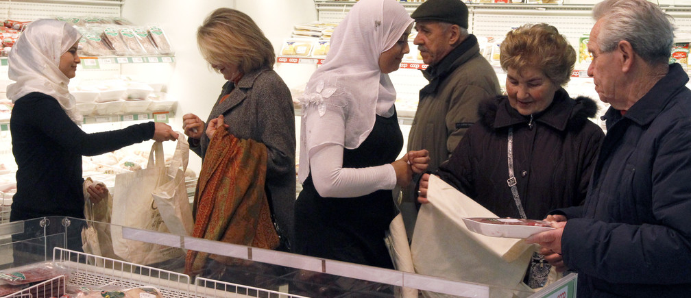 Moroccan women promote halal food in a Coop supermarket chain in Rome February 14, 2010. The supermarket, belonging to the Italian food retail chain Coop, started selling halal meat to allow increasing number of Muslim customers to buy meat killed in accordance with Islamic dietary laws.  REUTERS/Alessandro Bianchi        (ITALY - Tags: POLITICS SOCIETY FOOD BUSINESS) - RTR2A8CB
