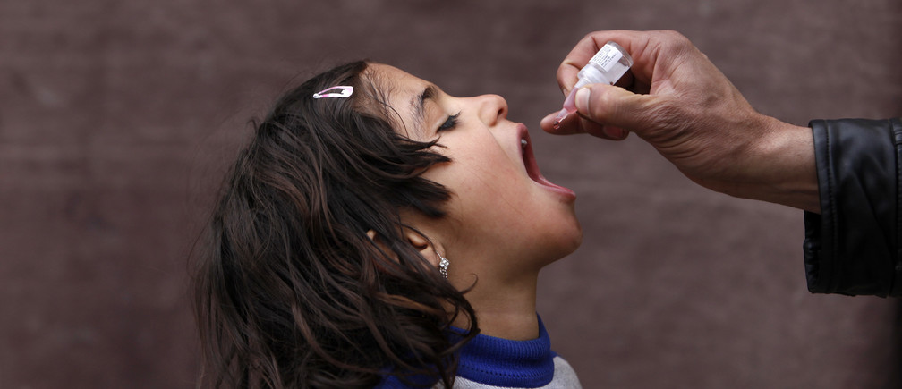 An Afghan child receives polio vaccination drops during an anti-polio campaign in Kabul March 24, 2014. REUTERS/Mohammad Ismail (AFGHANISTAN - Tags: HEALTH SOCIETY TPX IMAGES OF THE DAY) - GM1EA3O1NHO01