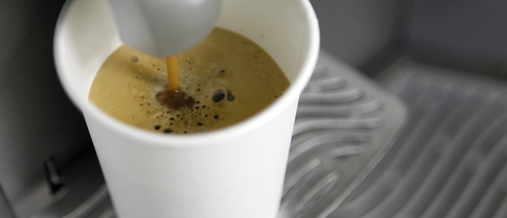 A coffee machine pours coffee into a paper cup in Kiev March 1, 2012.   REUTERS/Gleb Garanich (UKRAINE  - Tags: FOOD)   - RTR2YP01
