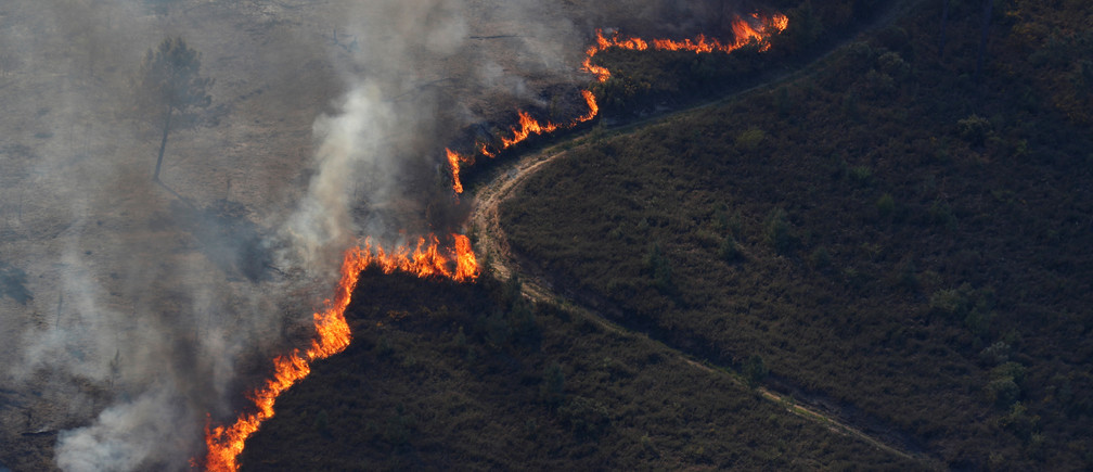 Flames of an approaching forest fire are seen near the small village of Gondomil, near Valenca, Portugal March 27, 2019. REUTERS/Rafael Marchante - RC17F0775100