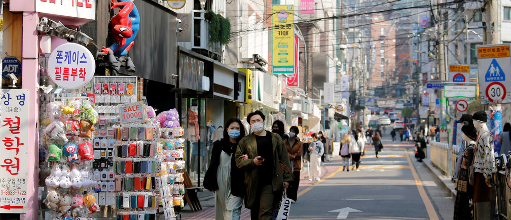 A couple wearing masks to protect against contracting the coronavirus disease (COVID-19) walk along a street in Seoul, South Korea, April 3, 2020.    REUTERS/Heo Ran - RC2YWF9Q93ZD
