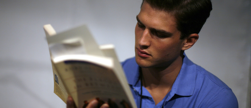 A model reads a book prior to the Spring 2008 Duckie Brown collection during New York Fashion Week September 5, 2007. REUTERS/Eric Thayer (UNITED STATES) - GM1DWBZZALAA