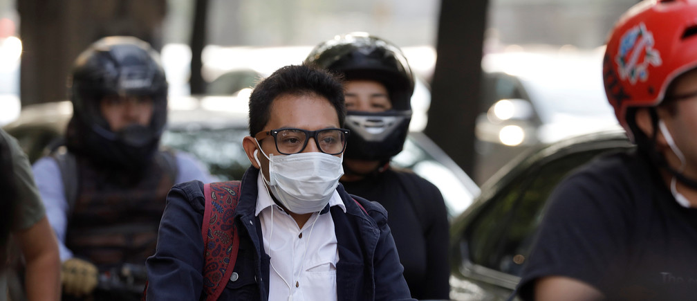 A man uses a face mask after authorities ordered schools in and around Mexico City to be closed on Thursday in an extraordinary step taken due to elevated levels of pollution in the smog-wreathed capital, in Mexico City, Mexico May 16, 2019. REUTERS/Luis Cortes