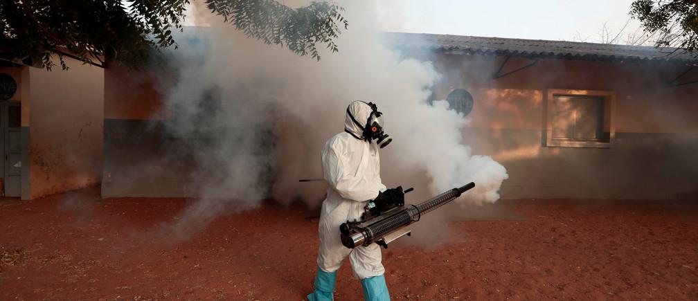 Un membre des services d'hygiène locaux porte une combinaison de protection et un masque facial, désinfecte une école vide pour arrêter la propagation de la maladie à coronavirus (COVID-19) à Dakar, Sénégal, le 1er avril 2020.