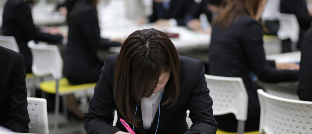 Japanese job-hunting students dressed in suits attend a business manners seminar at a placement centre in Tokyo May 28, 2012. With just over nine jobs awaiting every 10 of the 381,000 students graduating and looking for work this year, and the most coveted with the likes of Toyota or Nomura even more scarce, job-hunting has become fiercely competitive. The current heads of Japan's companies are often criticised for failing to keep pace with fleet-footed foreign rivals, but most are a product of that system and there is nothing to suggest it will change any time soon.Picture taken May 28, 2012. To match Insight JAPAN-ECONOMY/JOBS                 REUTERS/Toru Hanai (JAPAN - Tags: BUSINESS EMPLOYMENT) - GM1E86P00YV01