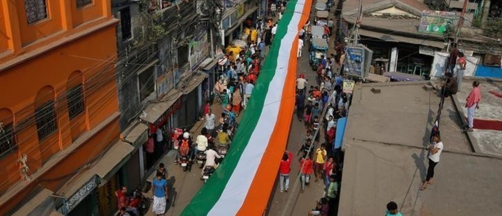 People carry an Indian national flag which according to organisers measures 1100 metres (3609 feet) through a street during Republic Day celebrations on the outskirts of Kolkata, India, January 26, 2019. REUTRS/Rupak De Chowdhuri
