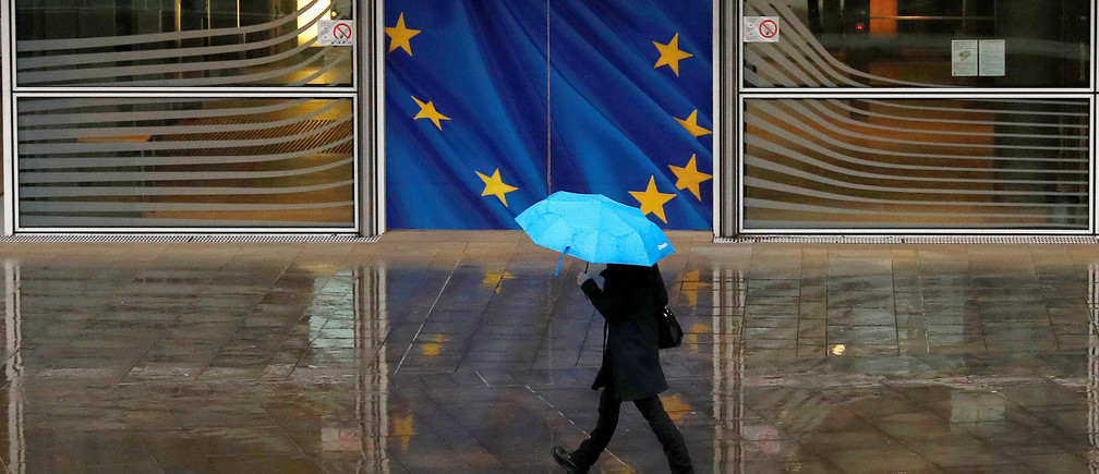 A woman holds an umbrella as she walks past the flag of the European Union outside the European Commission in Brussels, Belgium, December 13, 2017. REUTERS/Phil Noble - RC1C3CCB98C0