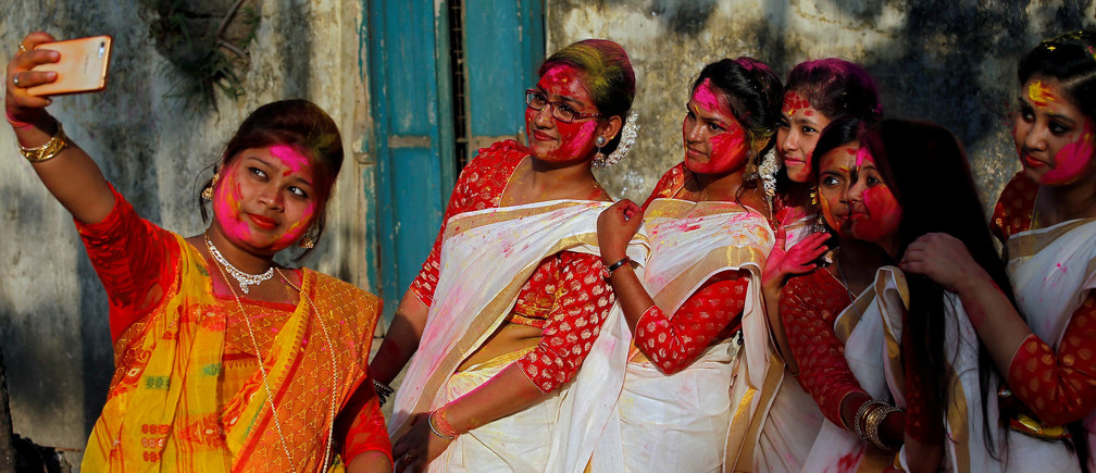 Students of Rabindra Bharati University, with their faces smeared in coloured powder, take a selfie during celebrations for Holi inside the university campus in Kolkata, India, February 26, 2018. REUTERS/Rupak De Chowdhuri     TPX IMAGES OF THE DAY - RC15DC63A560