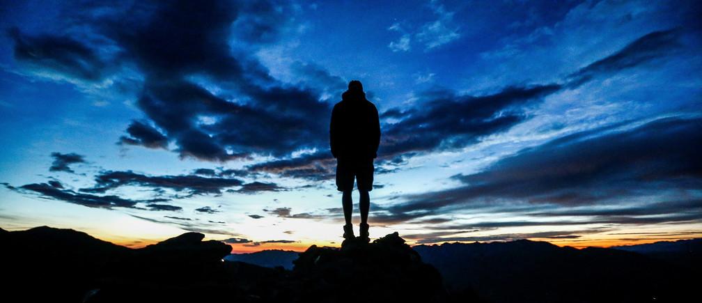 A man stands during sunrise on Kreuzjoch mountain in the Zillertal Alps in Schwendau, Austria July 11 2016.  REUTERS/ Dominic Ebenbichler  - D1BETOYPOWAA