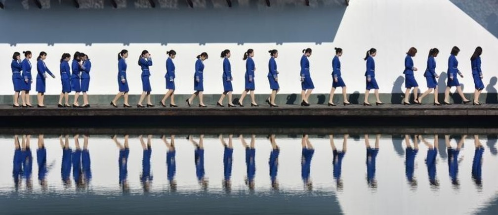 Attendants for the fifth World Internet Conference (WIC) are seen reflected in the water during a group photo session outside the venue, in Wuzhen town of Jiaxing, Zhejiang province, China November 9, 2018. REUTERS/Stringer  ATTENTION EDITORS - THIS IMAGE WAS PROVIDED BY A THIRD PARTY. CHINA OUT. - RC17A6A0C050