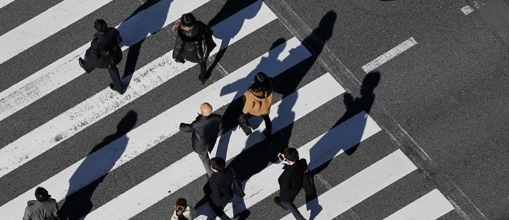 Pedestrians cast shadows on the crosswalk near the headquarters of the Bank of Japan in Tokyo December 19, 2014. The Bank of Japan maintained its massive monetary stimulus on Friday and offered a brighter view of the economy, clinging to hope that joint efforts with Prime Minister Shinzo Abe to revitalise the economy will prod companies into boosting wages and investment.