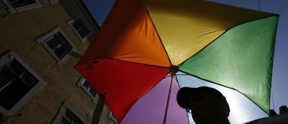 A man holds a umbrella with the colours of rainbow during the Gay Pride Parade in Lisbon June 28, 2008.   REUTERS/Nacho Doce (PORTUGAL) - GM1E46T0CNJ01