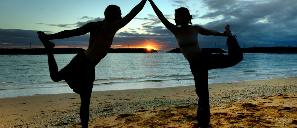 Darius Rustam, 30, and Tiffany Davis-Rustam (R) 27, from New York City, practice the King Dancer yoga pose during the sunset hours on Magic Island in Ala Moana Beach Park in Honolulu, Hawaii, January 21, 2004. The Rustams, both yoga instructors, are starting a tour of the Hawaiian Islands for five weeks. NO RIGHTS CLEARANCES OR PERMISSIONS ARE REQUIRED FOR THIS IMAGE REUTERS/Lucy Pemoni   LP/HK - RP4DRIHKDIAA