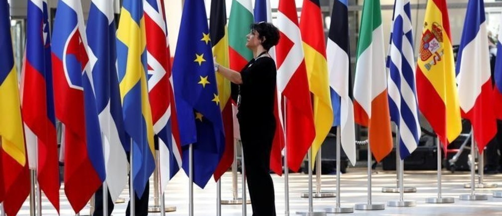 A woman adjusts flags ahead of European Union summit in Brussels, Belgium June 28, 2018.  REUTERS/Yves Herman - RC126CC1E8A0