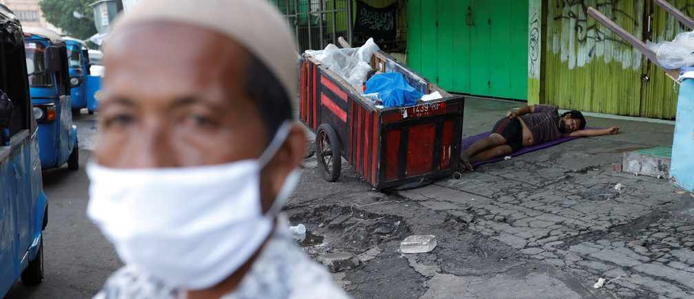 Homeless people sleep on a street while a street vendor wearing a face mask looks on outside a closed store, amid coronavirus disease (COVID-19) outbreak, at Tanah Abang textile market in Jakarta, Indonesia, March 31, 2020. REUTERS/Willy Kurniawan - RC2VUF91YDZ9