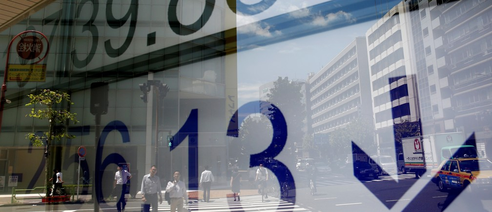 People are reflected on an electronic board showing Japan's Nikkei average outside a brokerage at a business district in Tokyo, Japan August 9, 2017.