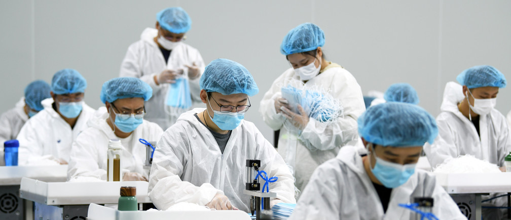 Employees work on a production line of surgical masks for export, at a railway equipment manufacturing company in Nanchang, Jiangxi province, China April 8, 2020. Picture taken April 8, 2020. China Daily via REUTERS  ATTENTION EDITORS - THIS IMAGE WAS PROVIDED BY A THIRD PARTY. CHINA OUT. - RC2U0G91RT4J