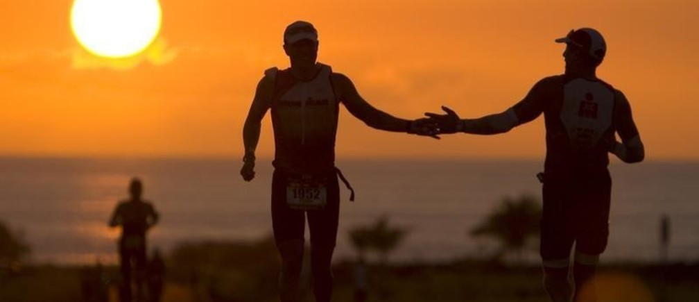 """Steven Pressman of the U.S. (C) slaps hands as he passes another runner near the half way point at the """"Energy Lab"""" on the marathon section of the Ford Ironman World Championship triathlon in Kailua-Kona, Hawaii October 9, 2010. REUTERS/Hugh Gentry(UNITED STATES - Tags: SPORT TRIATHLON) - GM1E6AA18HB01"""