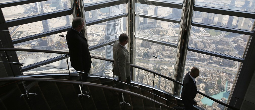 Businessmen walk down the stairs at the 123rd floor of the Burj Khalifa, the tallest building in the world, in Dubai November 19, 2014.
