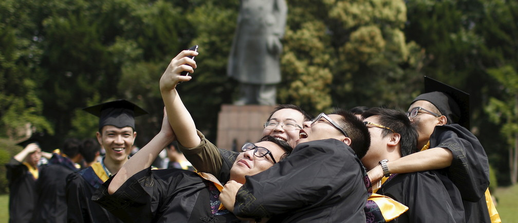 Graduates, in academic dress, take a 'selfie' in front of a statue.