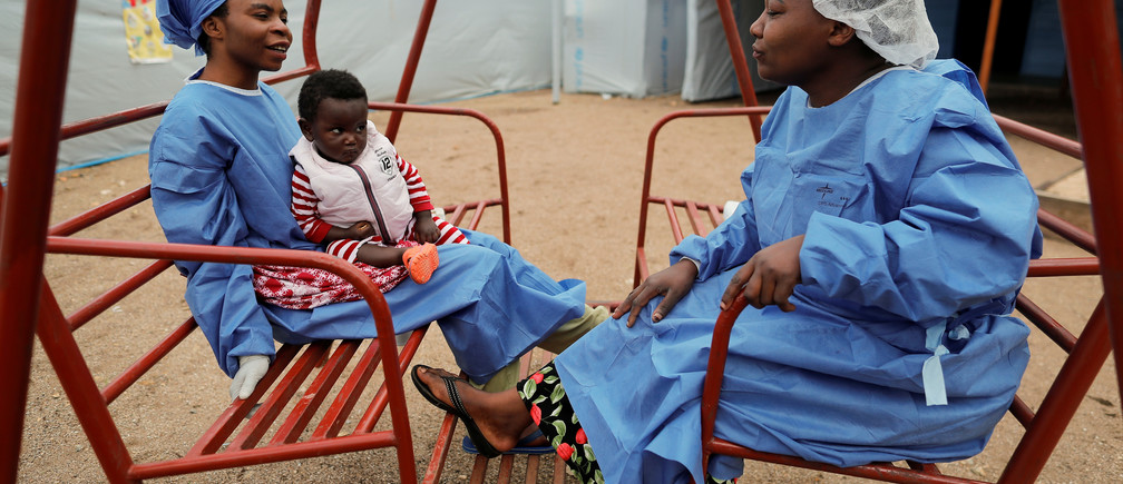 "Noella Kavira Kitakya, 26, holding 16-month-old Kambale Eloge, whose mother died of Ebola, talks to Arlette Kavugho, 40, mother of six, in the courtyard of United Nations Children's Fund (UNICEF) creche for children whose families are suspected or confirmed Ebola cases, next to an Ebola treatment centre (ETC) in Katwa, near Butembo, in the Democratic Republic of Congo, October 2, 2019. Both women are Ebola survivors who now work as caregivers. Kavira survived Ebola last June with her two brothers but their mother and close family members succumbed to the virus. ""I am often afraid to relapse but I was reassured that once victorious, there is no risk,"" she said. ""I was treated effectively and it allowed me to heal. Others did not have the same luck,"" she added. ""It is sad to see children becoming orphans because of Ebola."" REUTERS/Zohra Bensemra   SEARCH ""EBOLA ZOHRA"" FOR THIS STORY. SEARCH ""WIDER IMAGE"" FOR ALL STORIES. - RC12146CFD40"