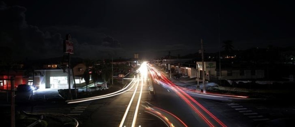 Cars drive in the darkness in a neighbourhood that has no electricity, after Hurricane Maria in Caguas, Puerto Rico October 4, 2017. Picture taken with long exposure.  REUTERS/Carlos Barria