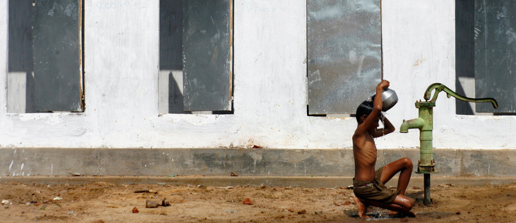 A boy takes bath outside newly built toilets in a village on the outskirts of Nagapattinam, about 325km (202 miles) from the southern Indian city of Chennai December 24, 2005. Government and multilateral agencies have pledged more than $7.3 billion in aid for nations hit by the December 26, 2004 earthquake and tsunami in the Indian Ocean, while global private donations amount to more than $5.7 billion. REUTERS/Jagadeesh NV - RP2DSFINHWAC