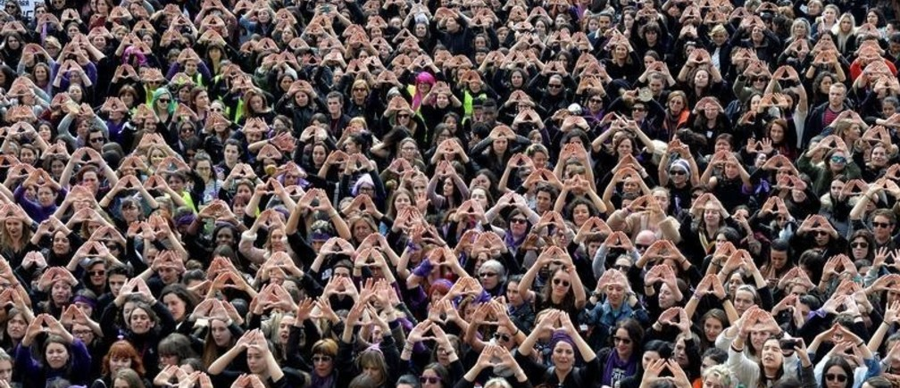 Protesters form triangles with their hands during a demonstration for women's rights in Bilbao, Spain, March 8, 2018, on International Women's Day.