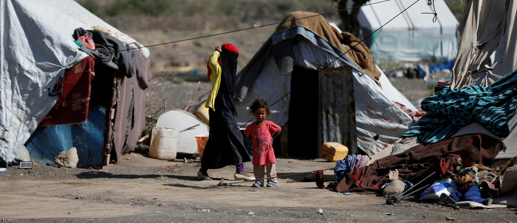 A woman walks past a child at a camp for people displaced by the war, near Sanaa, Yemen April 25, 2017. REUTERS/Khaled Abdullah - RTS13T4O