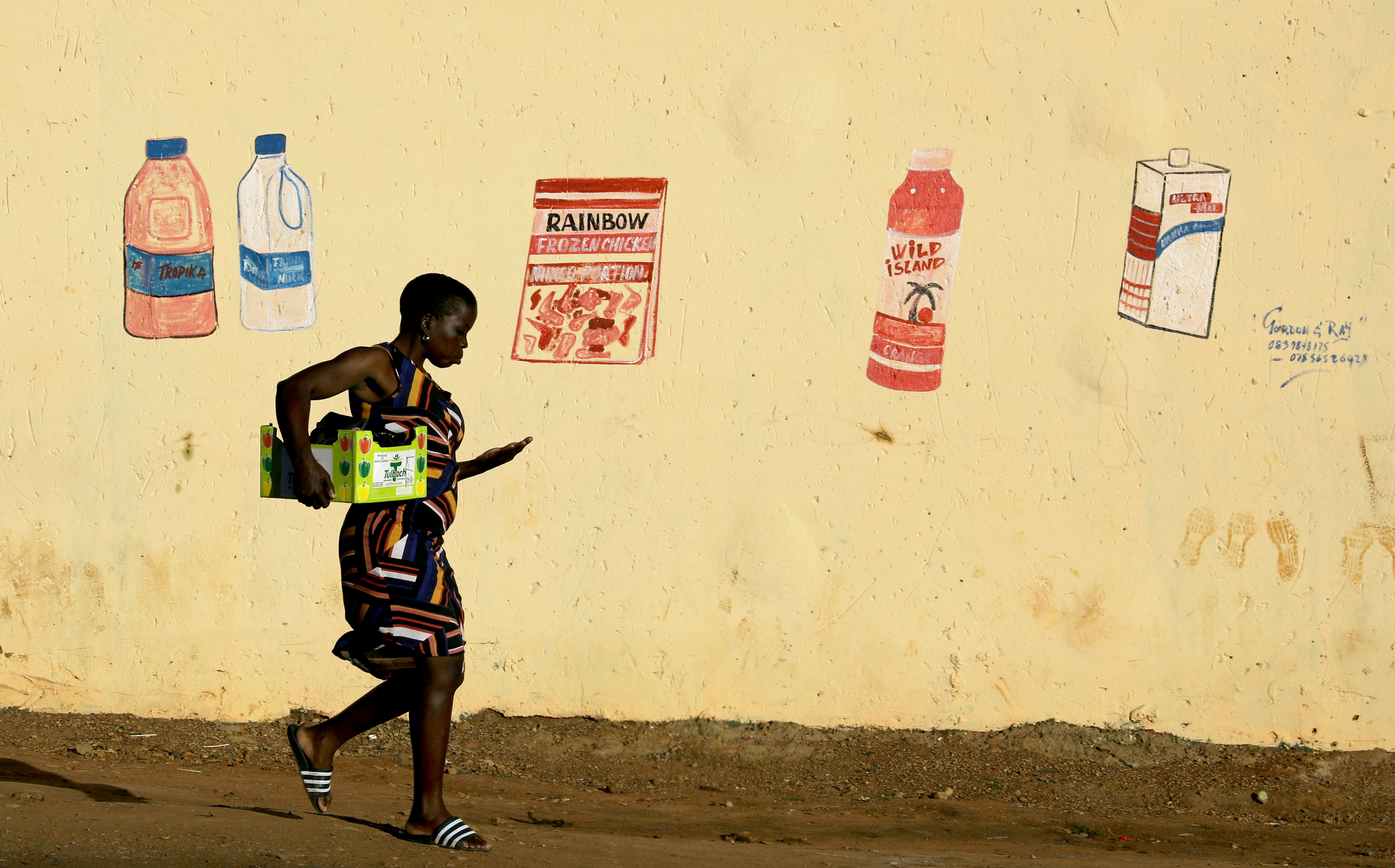 A woman counts her change as she leaves a convenience store in  South Africa
