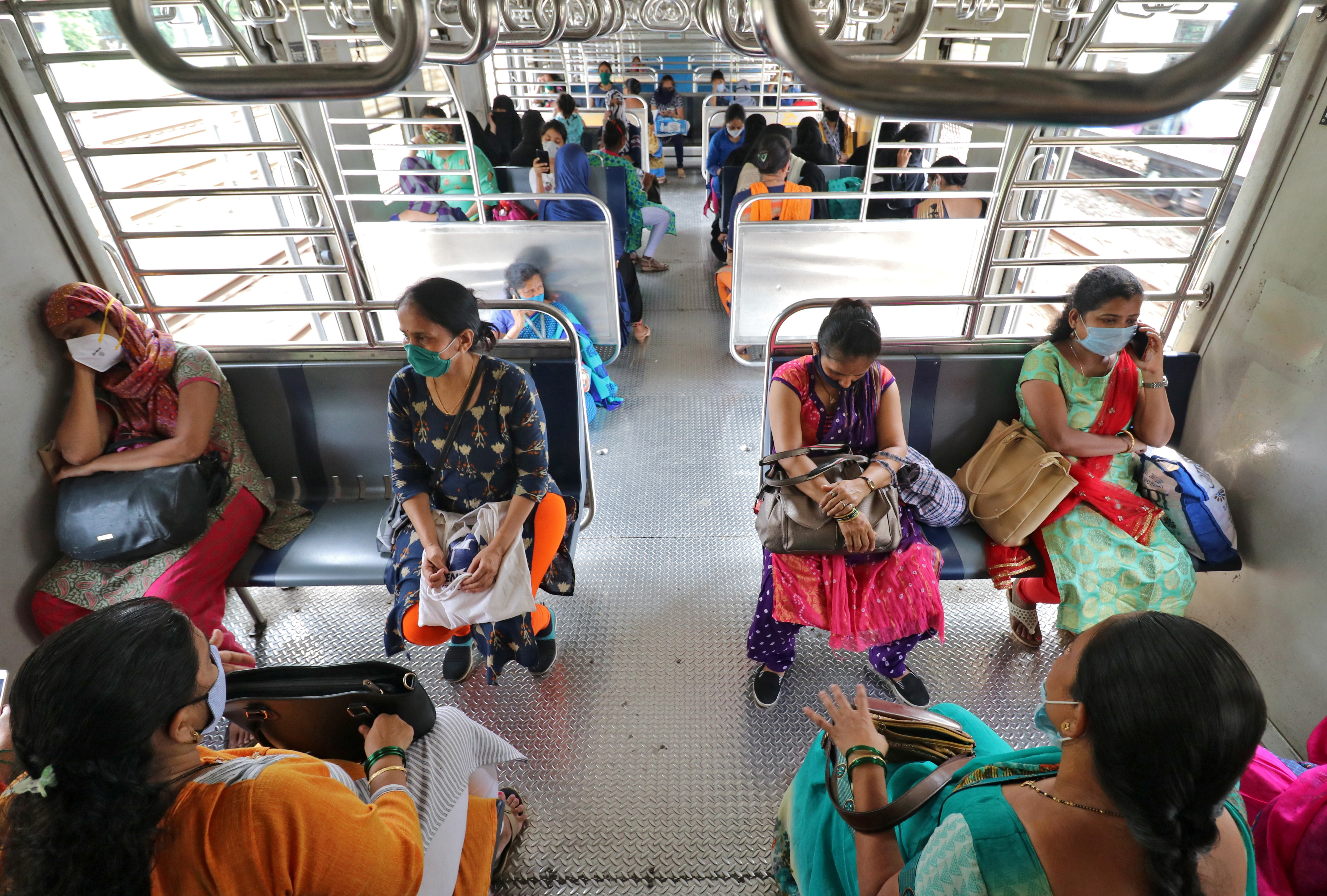 Women wearing protective face masks commute in a suburban train after authorities resumed the train services for women passengers during non-peak hours, amidst the coronavirus disease (COVID-19) outbreak, in Mumbai, India, October 21, 2020.