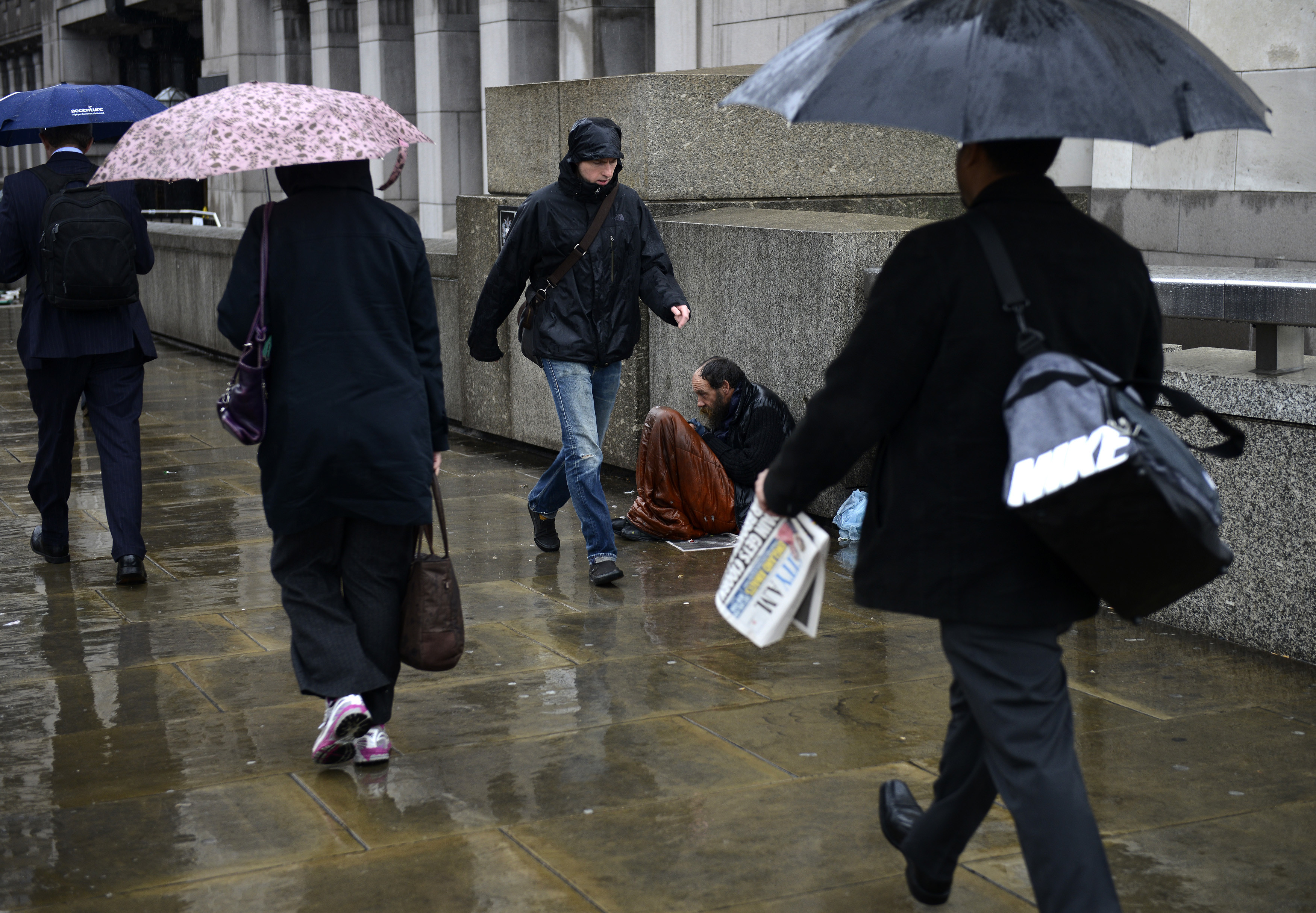 A homeless man sits in the rain as commuters make their way to work across London Bridge