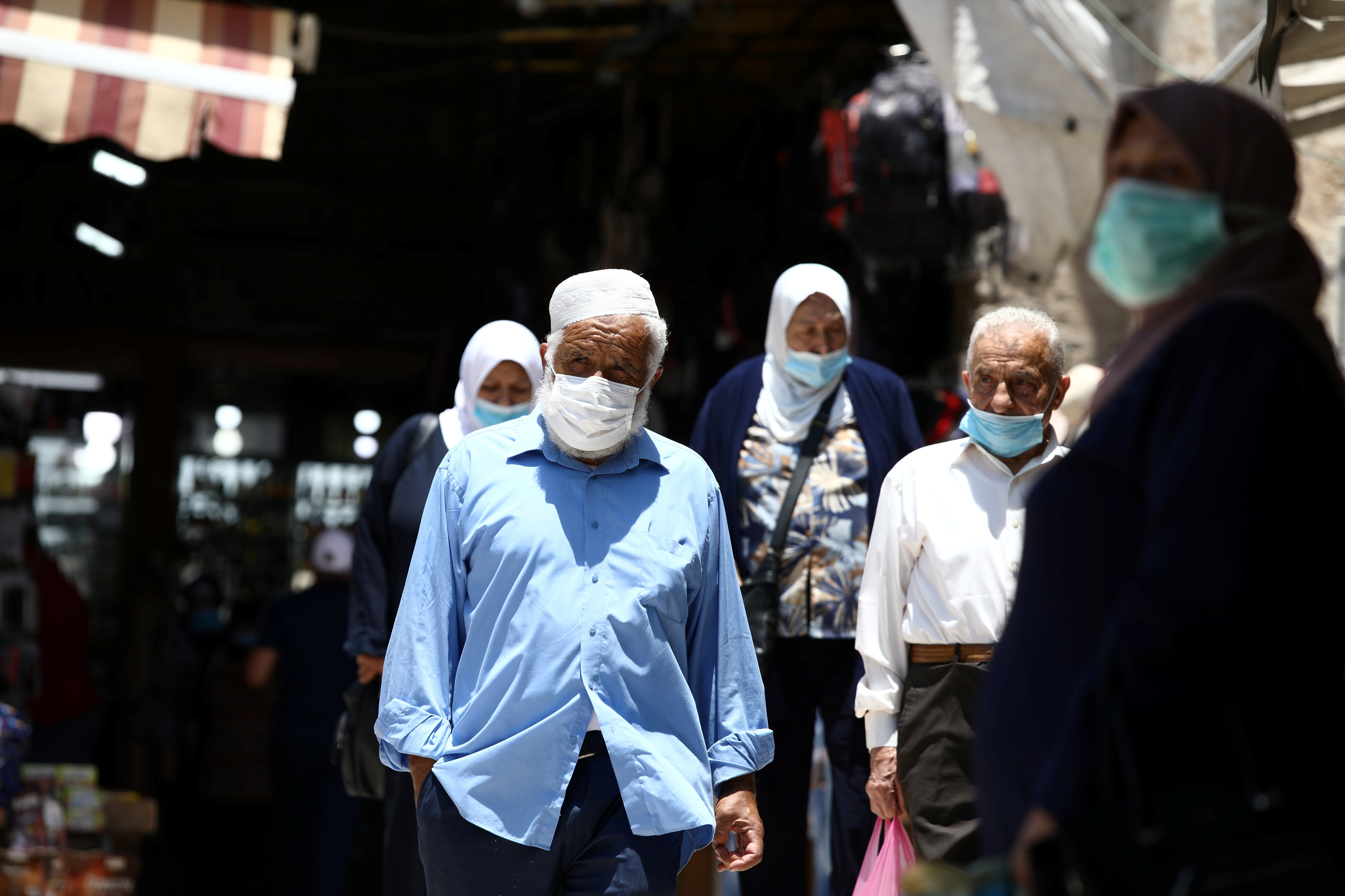 People wearing face masks to help fight the spread of the coronavirus disease (COVID-19) walk past shops in a market in Jerusalem's Old City July 6, 2020. REUTERS/Ammar Awad - RC2NNH99644G