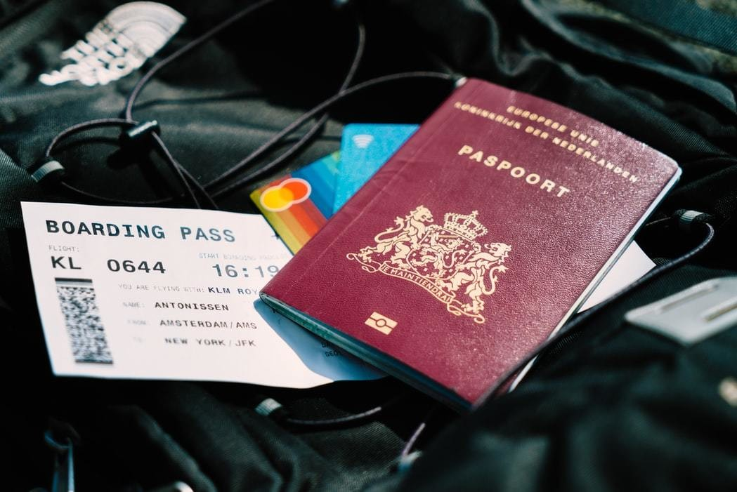 A paper-nased passport is pictured with a boarding pass.