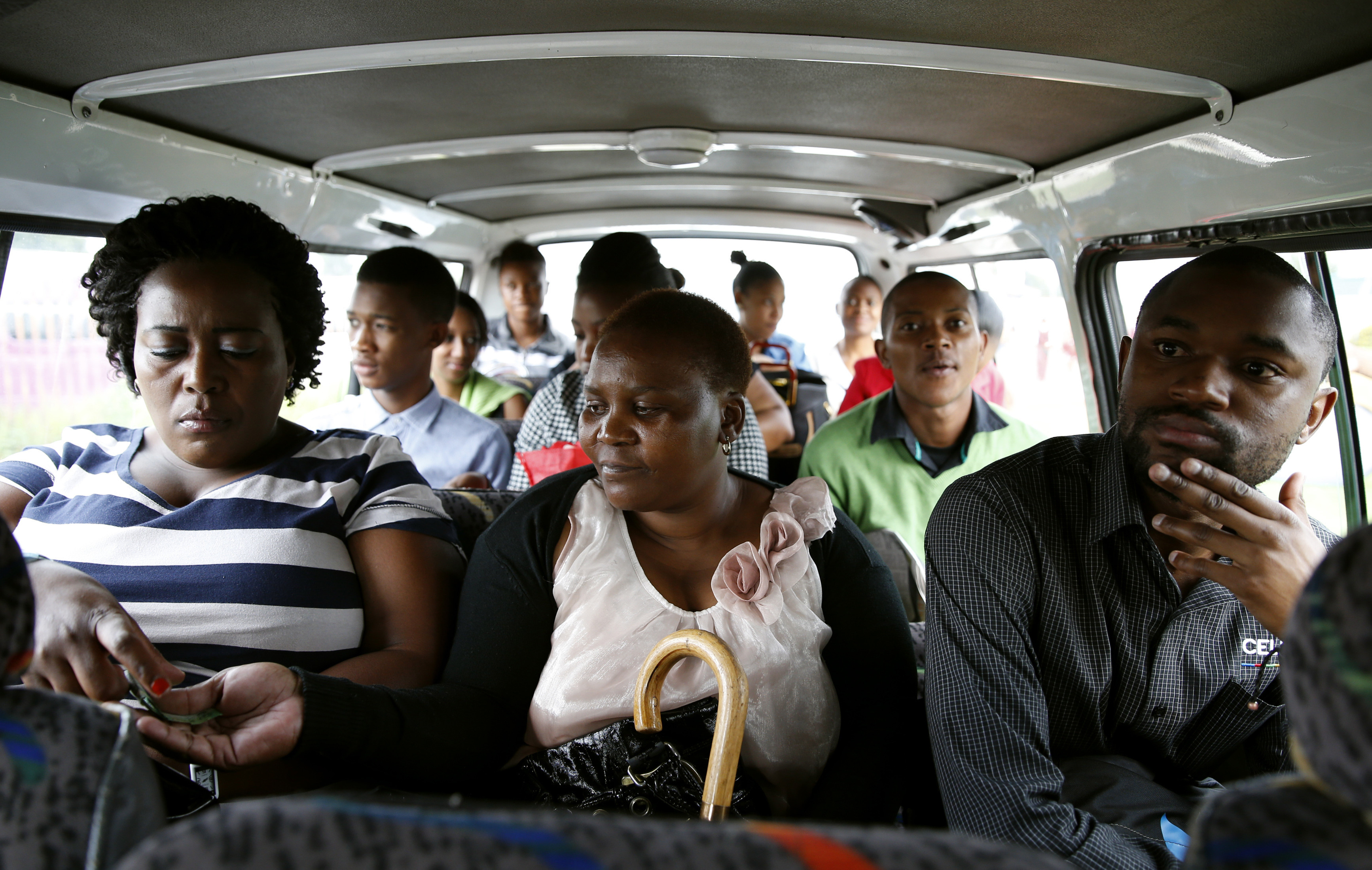 Passengers pass their fares to minibus taxi driver Zakes Hadebe as they commute from Soweto township to central Johannesburg February 21, 2014. South Africa's minibus taxi industry, scorned by other motorists for reckless driving and dogged by a reputation for violence, moves 15 million people every day, most of them lower income blacks. More like buses than the taxis of New York or London, the rumbling 16-seaters are the wheels of Africa's largest economy. Picture taken February 21.