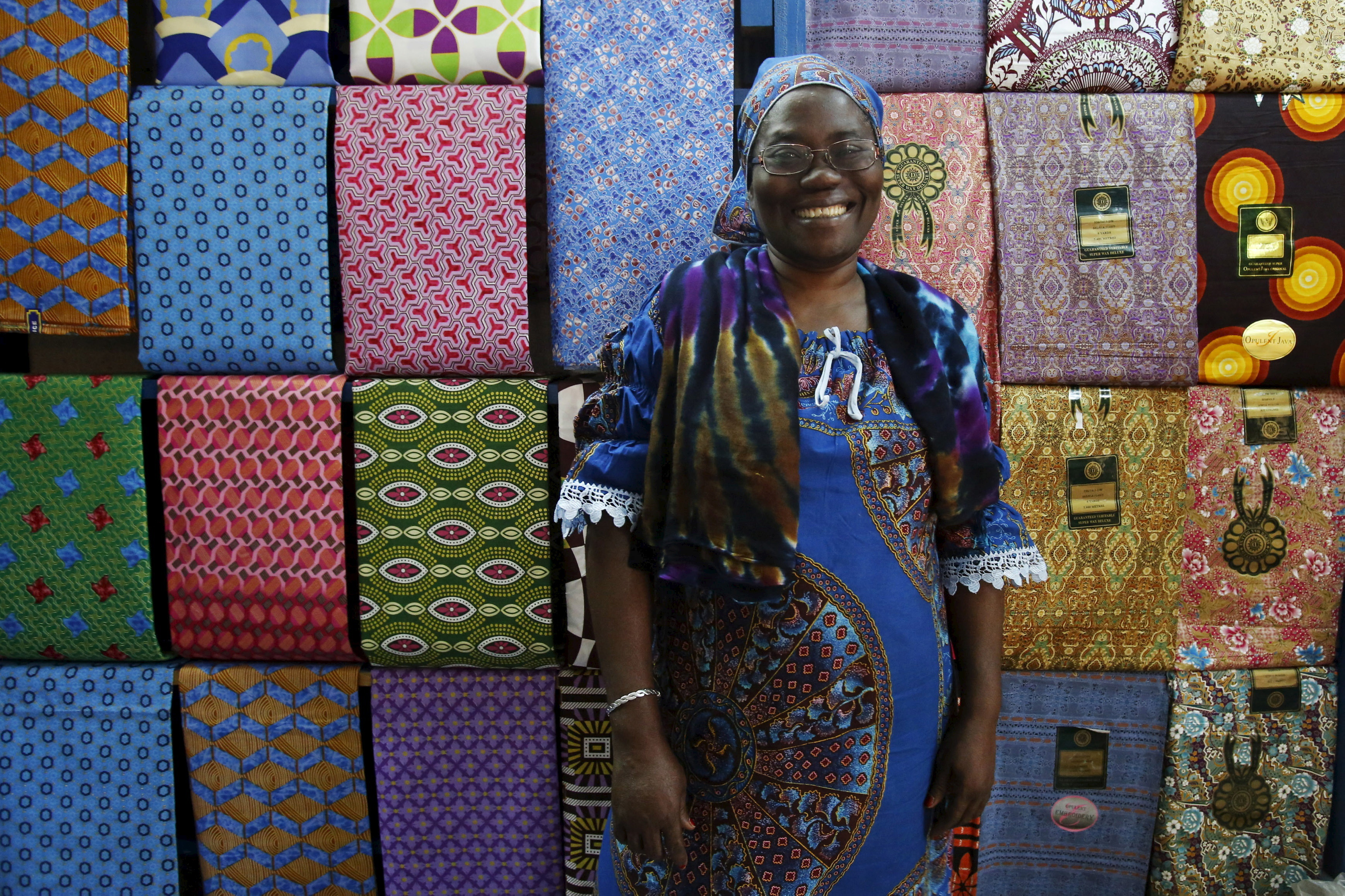 "Fofanan Man, a 59-year-old businesswoman, poses for a photograph in front of textiles in her shop in Bouake, Ivory Coast, February 10, 2016. Women have long played a dominant role in agriculture in Ivory Coast and in the sprawling markets where most Ivorians purchase their daily necessities. Now some are breaking through into the most important positions in government, administration and business - positions long held by males in this traditional society. In 2012, Niale Kaba became finance minister, the first woman to hold the post in more than half a century as an independent nation. Ivorian women today work in a range of jobs – from gas-station attendant to plastic recycler and lawyer. International Women's Day is marked on March 8. REUTERS/Thierry Gouegnon SEARCH ""THE WIDER IMAGE"" FOR ALL STORIES - GF10000336765"