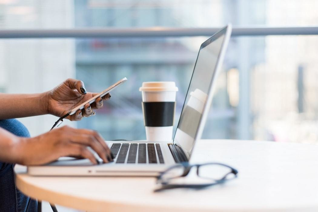 The hands of a Black person are seen typing at a computer, with a phone and coffee cup also in shot.