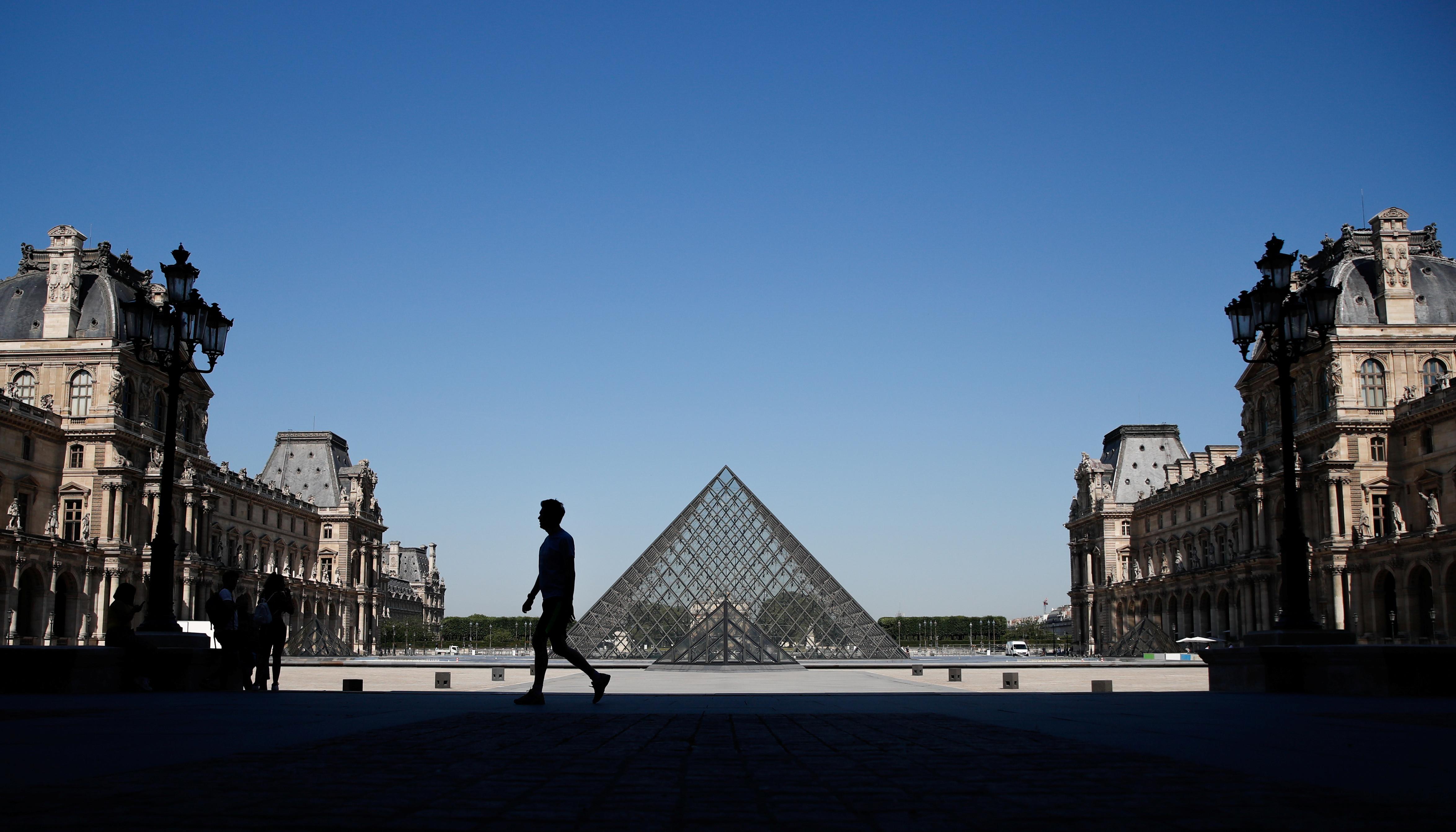 A man walks near the Louvre Pyramid