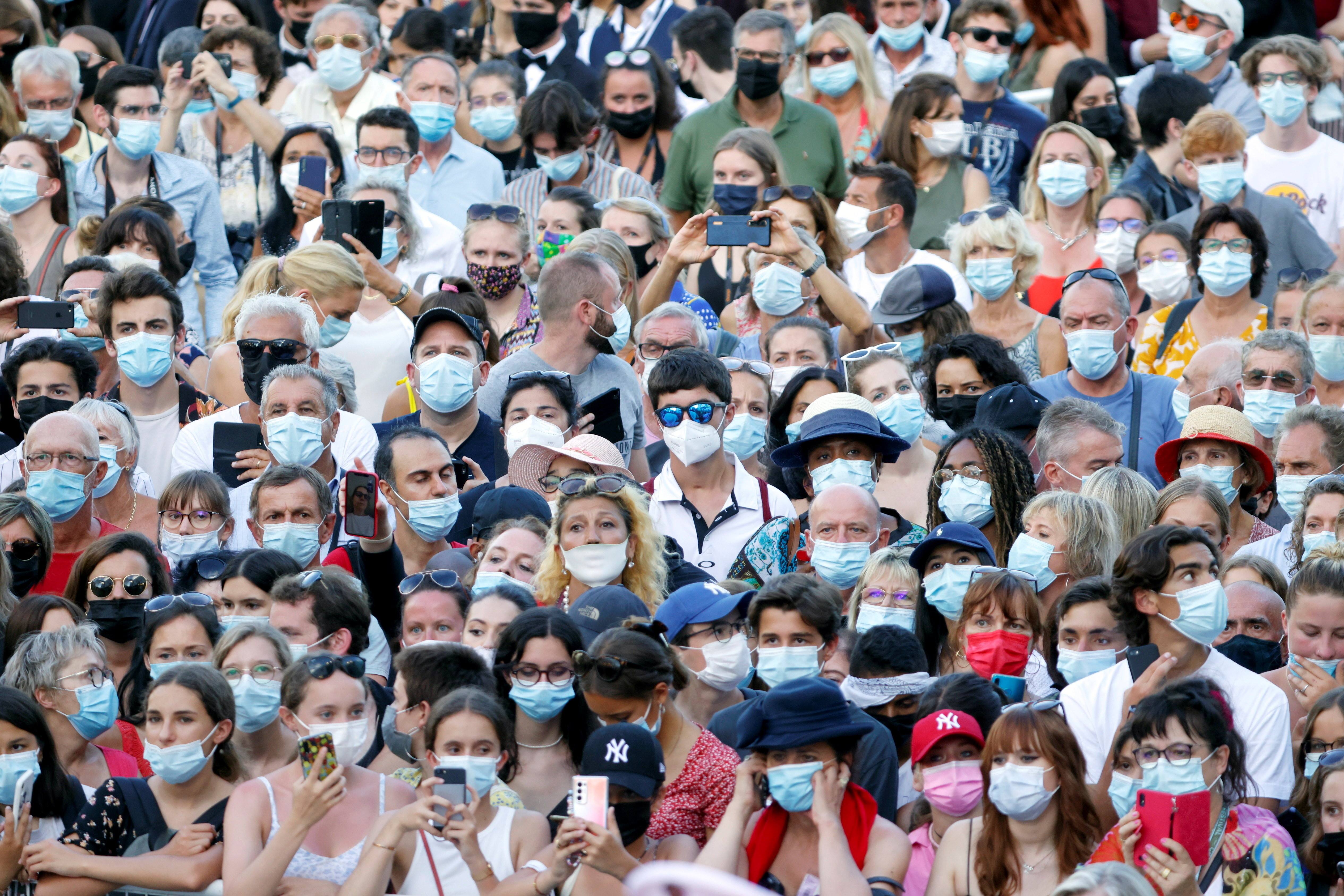 """The 74th Cannes Film Festival - Closing ceremony and screening of the film """"OSS 117: Alerte Rouge en Afrique Noire"""" (OSS 117: From Africa with Love) out of competition - Red Carpet Arrivals - Cannes, France, July 17, 2021. Cinema fans wearing protective face masks watch guests' arrivals. REUTERS/Eric Gaillard     TPX IMAGES OF THE DAY - UP1EH7H1B8ILH"""